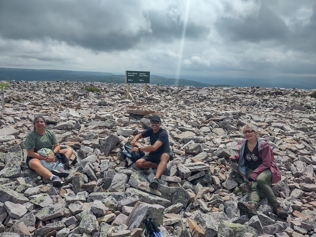 hikers sitting on top of gros morne mountain